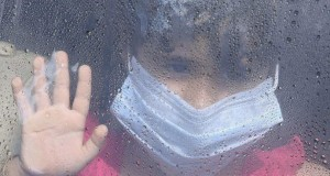 A girl wearing a mask looks out a car window as rain drops are seen in Taif