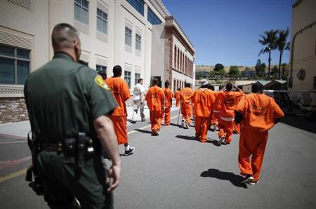 Inmates are escorted by a guard